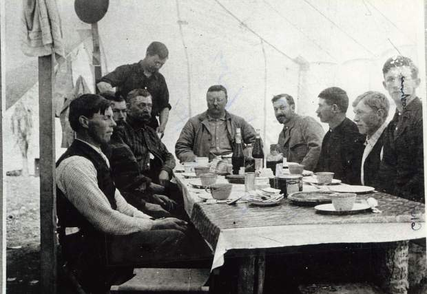 Teddy Roosevelt is pictured at the back end of the table, center, at Divide Creek Camp in 1905.