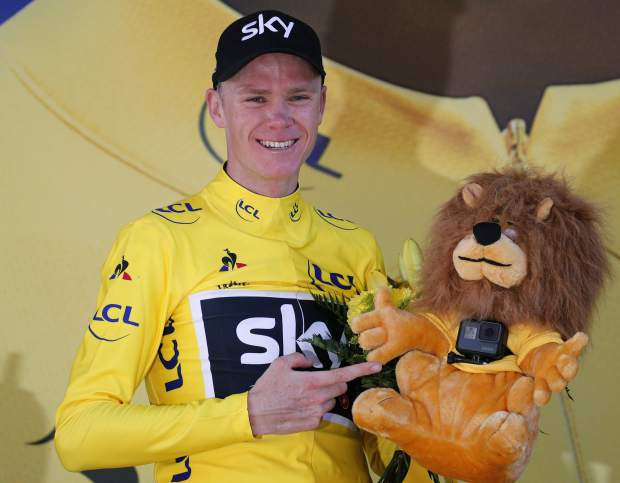 Britain's Chris Froome, wearing the overall leader's yellow jersey, points at the small camera attached to the yellow jersey's mascot on the podium of the fifteenth stage of the Tour de France cycling race over 189.5 kilometers (117.8 miles) with start in Laissac-Severac l'Eglise and finish in Le Puy-en-Velay, France, Sunday, July 16, 2017. (AP Photo/Christophe Ena)