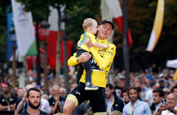 Tour de France winner Britain's Chris Froome, wearing the overall leader's yellow jersey, holds his son Kellan on the podium after the twenty-first and last stage of the Tour de France cycling race over 103 kilometers (64 miles) with start in Montgeron and finish in Paris, France, Sunday, July 23, 2017. (AP Photo/Thibault Camus)