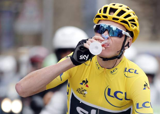 Britain's Chris Froome, wearing the overall leader's yellow jersey drinks a cup of Champagne during the twenty-first and last stage of the Tour de France cycling race over 103 kilometers (64 miles) with start in Montgeron and finish in Paris, France, Sunday, July 23, 2017. (Benoit Tessier, Pool via AP)