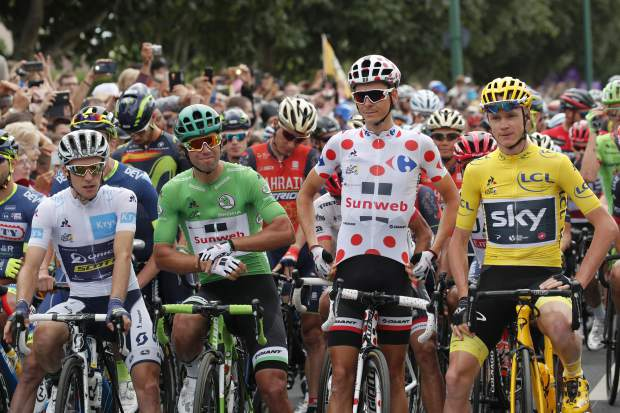 Britain's Chris Froome, wearing the overall leader's yellow jersey, Australia's Michael Matthews, wearing the best sprinter's green jersey, France's Warren Barguil, wearing the best climber's dotted jersey and Britain's Simon Yates, wearing the best young rider's white jersey, wait for the start of the twenty-first and last stage of the Tour de France cycling race over 103 kilometers (64 miles) with start in Montgeron and finish in Paris, France, Sunday, July 23, 2017. (AP Photo/Christophe Ena)
