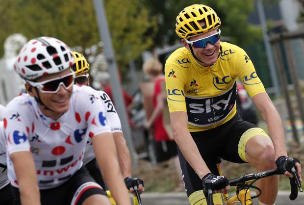 Britain's Chris Froome, wearing the overall leader's yellow jersey, and France's Warren Barguil, wearing the best climber's dotted jersey, ride during the twenty-first and last stage of the Tour de France cycling race over 103 kilometers (64 miles) with start in Montgeron and finish in Paris, France, Sunday, July 23, 2017. (AP Photo/Christophe Ena)