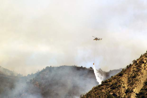 A helicopter drops water on a fire that broke out late Monday afternoon along the Grand Hogback east of New Castle, adjacent to Garfield County Road 335.