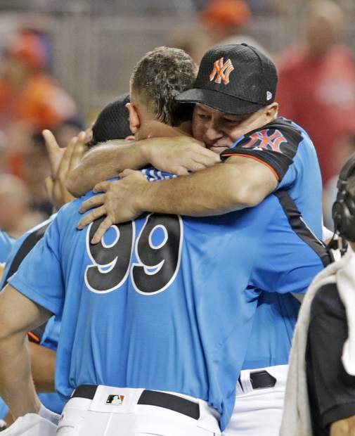 New York Yankees' Aaron Judge (99) is hugged by Danilo Valentine, right, during the MLB baseball All-Star Home Run Derby, Monday, July 10, 2017, in Miami. (AP Photo/Lynne Sladky)