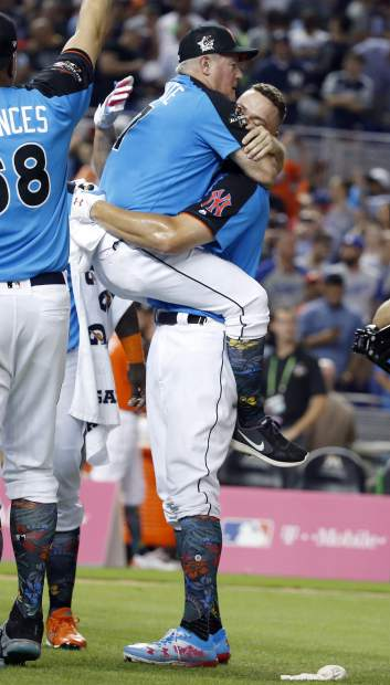 New York Yankees coach Danilo Valentine, left, jumps on Aaron Judge, right, after Judge dominated in the MLB baseball All-Star Home Run Derby, Monday, July 10, 2017, in Miami. (AP Photo/Wilfredo Lee)