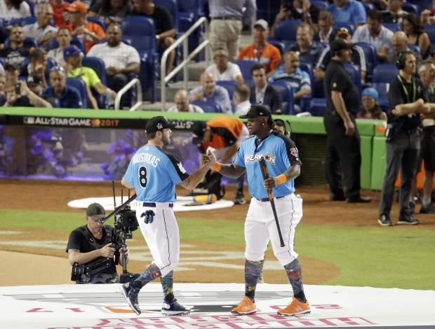 Kansas City Royals' Mike Moustakas, left, and Minnesota Twins' Miguel Sano, right, exchange greetings during the MLB baseball All-Star Home Run Derby opening ceremony, Monday, July 10, 2017, in Miami. (AP Photo/Lynne Sladky)