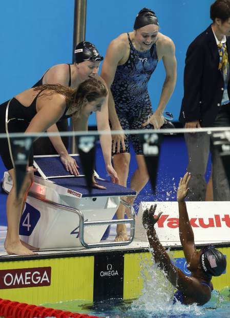 United States' Simone Manuel, bottom, and her teammates , top from left, Kathleen Baker, Lilly King and Kelsi Worrell celebrate after setting a new world record in the women's 4x100-meter medley relay during the swimming competitions of the World Aquatics Championships in Budapest, Hungary, Sunday, July 30, 2017. (AP Photo/Petr David Josek)