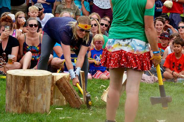 Moving in to assist a struggling competitor, Heather Henry forcefully smashes up a stubborn log in the women's wood splitting competition.