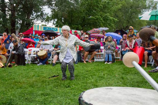 Laurie Loeb leads the Rhythm of the Heart Community Drum Circle at the opening ceremony of the 46th Annual Carbondale Mountain Fair. A large crowd participated in the drum circle despite heavy rains that swept through Carbondale in the early evening.