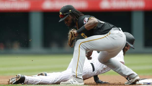 Pittsburgh Pirates first baseman Josh Bell, top, fields a pickoff throw as Colorado Rockies' Charlie Blackmon dives back into first base in the first inning of a baseball game Sunday, July 23, 2017, in Denver. (AP Photo/David Zalubowski)