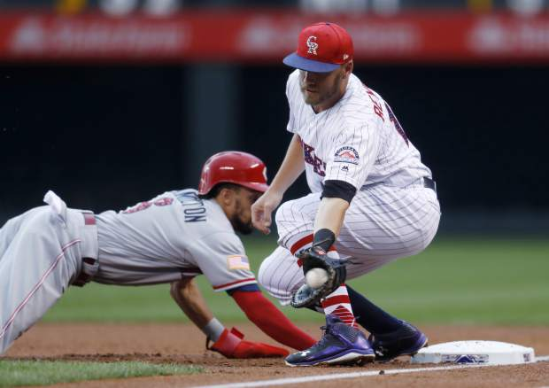 Colorado Rockies first baseman Mark Reynolds, front, fields a pickoff throw as Cincinnati Reds' Billy Hamilton dives back into first base before getting tagged in the first inning of a baseball game Tuesday, July 4, 2017, in Denver. (AP Photo/David Zalubowski)