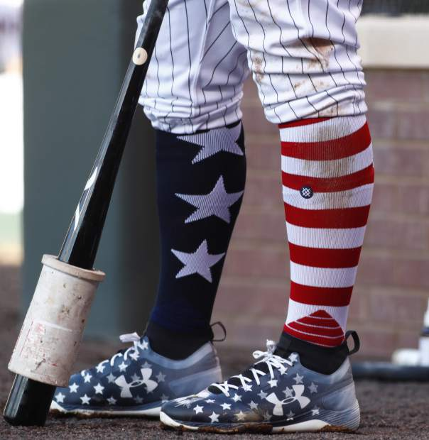 To mark the spirit of the July Fourth holiday, Colorado Rockies' Mark Reynolds wears a colorful pair of patriotic socks and shoes as he waits to bat against the Cincinnati Reds in the first inning of a baseball game Monday, July 3, 2017, in Denver. (AP Photo/David Zalubowski)