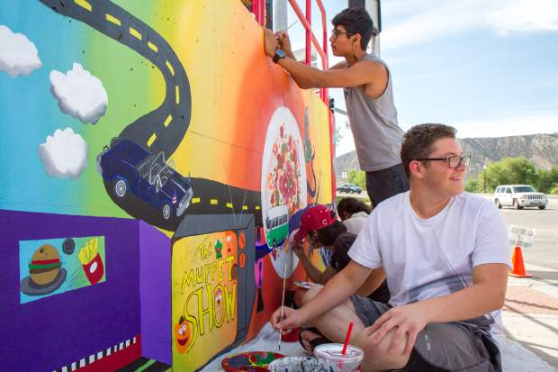 Trevor Green works on his piece of the mural infront of the Kum and Go in Rifle.
