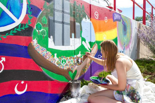 Kaitlyn Molimari paints on her portion of the mural infront of the Kum and Go gas station in Rifle.