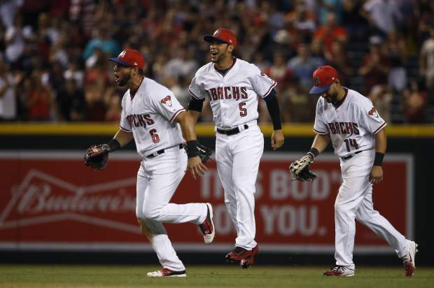Arizona Diamondbacks' David Peralta (6), Gregor Blanco (5) and Reymond Fuentes (14) celebrate after the final out of the ninth inning of a baseball game against the Colorado Rockies Saturday, July 1, 2017, in Phoenix. The Diamondbacks defeated the Rockies 6-2. (AP Photo/Ross D. Franklin)