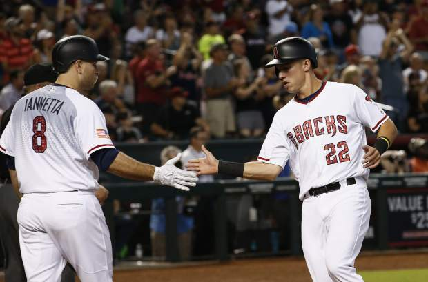 Arizona Diamondbacks' Jake Lamb (22) celebrates his run scored against the Colorado Rockies with Chris Iannetta (8) during the sixth inning of a baseball game, Sunday, July 2, 2017, in Phoenix. (AP Photo/Ross D. Franklin)
