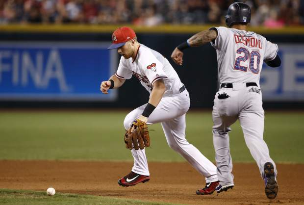 Arizona Diamondbacks' Brandon Drury, left, is unable to field a grounder hit by Colorado Rockies' Raimel Tapia as Rockies' Ian Desmond (20) runs to second base during the fourth inning of a baseball game, Sunday, July 2, 2017, in Phoenix. (AP Photo/Ross D. Franklin)