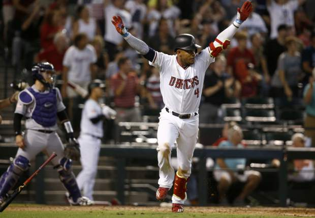 Arizona Diamondbacks' Ketel Marte (4) celebrates his walk off single against the Colorado Rockies as Rockies catcher Tony Wolters, left, looks on during the ninth inning of a baseball game, Sunday, July 2, 2017, in Phoenix. The Diamondbacks defeated the Rockies 4-3. (AP Photo/Ross D. Franklin)