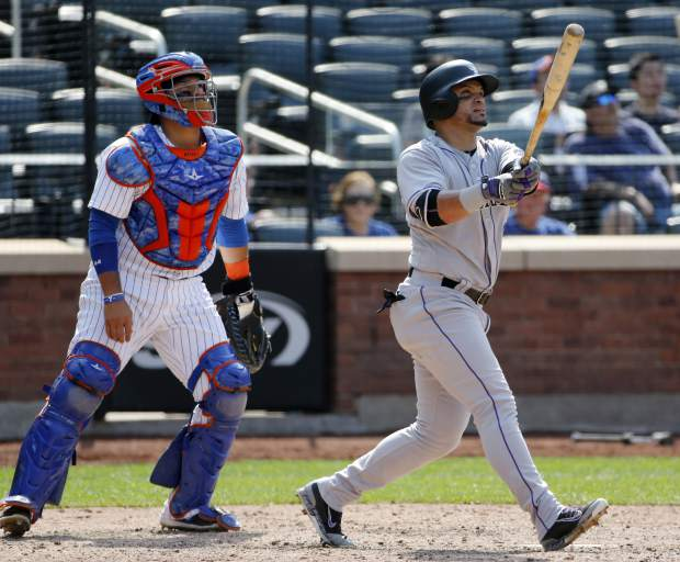 New York Mets catcher Rene Rivera, left, watches as Colorado Rockies' Gerardo Parra, right, hits an eighth-inning two-run home run in a baseball game Sunday, July 16, 2017, in New York. (AP Photo/Kathy Willens)