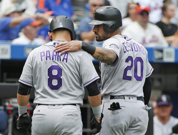 Colorado Rockies Ian Desmond (20) puts his arm around Colorado Rockies' Gerardo Parra (8) after the pair scored on Trevor Story's first-inning, two-run double in a baseball game against the New York Mets, Sunday, July 16, 2017, in New York. (AP Photo/Kathy Willens)