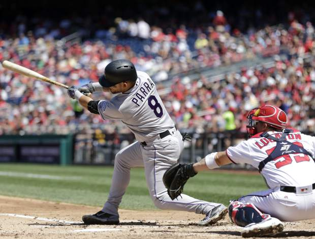 Colorado Rockies' Gerardo Parra (8) hits an RBI ground-out during the third inning of a baseball game against the Washington Nationals, Sunday, July 30, 2017, in Washington. (AP Photo/Mark Tenally)