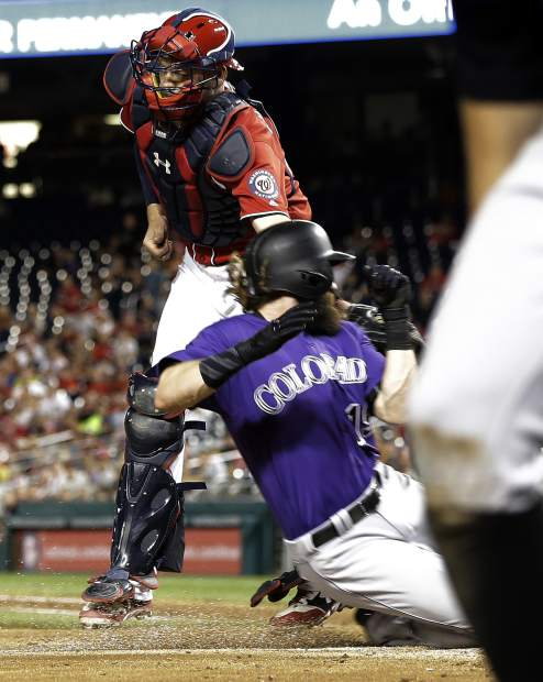 Colorado Rockies' Charlie Blackmon, bottom, is tagged out by Washington Nationals catcher Matt Wieters, top, during the fifth inning of the second game of a split doubleheader baseball game Sunday, July 30, 2017, in Washington. (AP Photo/Mark Tenally)