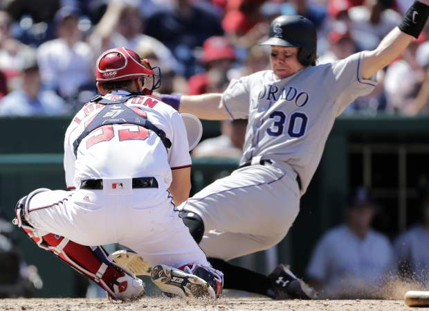 Colorado Rockies' Ryan Hanigan, right, is tagged out at home plate by Washington Nationals catcher Jose Lobaton, left, during the fourth inning of a baseball game between the Colorado Rockies and Washington Nationals, Sunday, July 30, 2017, in Washington. (AP Photo/Mark Tenally)