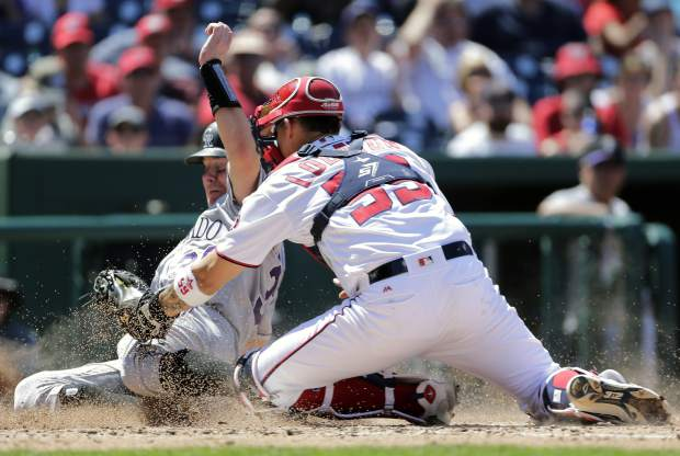 Colorado Rockies' Ryan Hanigan, left, is tagged out at home plate by Washington Nationals catcher Jose Lobaton during the fourth inning of a baseball game Sunday, July 30, 2017, in Washington. (AP Photo/Mark Tenally)