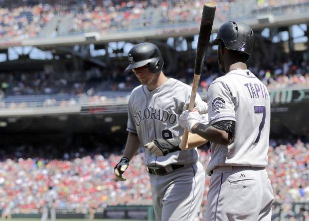 Colorado Rockies' DJ LeMahieu, center, celebrates with Colorado Rockies' Raimel Tapia, right, after scoring on a RBI by Colorado Rockies' Gerardo Parra during the third inning of a baseball game between the Colorado Rockies and Washington Nationals, Sunday, July 30, 2017, in Washington. (AP Photo/Mark Tenally)