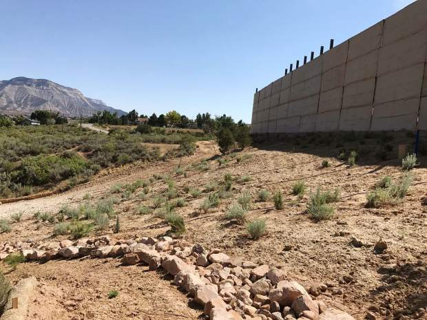 A sound wall sorrounds the BMC D Pad with landscaping that includes shrubbery, recently planted trees, and grass that has been seeded. There is also a line of rock armor outside the pad to ensure that all of the sediment gets out of any water runoff.