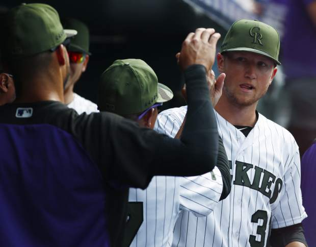 Colorado Rockies' Ian Desmond, front, and first base coach Tony Diaz, center, congratulate starting pitcher Kyle Freeland who returns to the dugout after giving up a single to Chicago White Sox's Melky Cabrera to break up Freeland's bid for a no hitter with one out in the ninth inning of a baseball game Sunday, July 9, 2017, in Denver. (AP Photo/David Zalubowski)