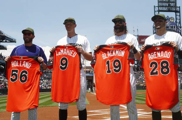 From left to right, Colorado Rockies relief pitcher Greg Holland, second baseman DJ LeMahieu, center fielder Charlie Blackmon and third baseman Nolan Arenado hold up their jerseys to mark their inclusion on the roster of the National League in the MLB All-Star Game as they took part in a ceremony before hosting the Chicago White Sox in a baseball game Sunday, July 9, 2017, in Denver. (AP Photo/David Zalubowski)