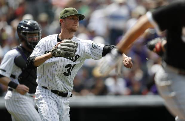 Colorado Rockies starting pitcher Kyle Freeland, center, throws to first base to put out Chicago White Sox' Carlos Rodon, front, after he put down a sacrifice bunt in the sixth inning of a baseball game Sunday, July 9, 2017, in Denver. Rockies archer Ryan Hanigan, back, looks on. The Rockies won 10-0. (AP Photo/David Zalubowski)