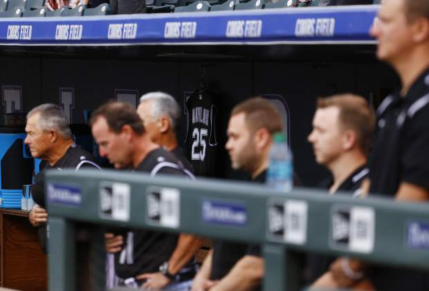 The jersey of former Colorado Rockies manager Don Baylor hangs in the dugout as members of the Colorado Rockies bow their heads in a moment of silence before a baseball game against the Atlanta Braves Monday, Aug. 14, 2017, in Denver. Baylor died Aug. 7, 2017. (AP Photo/Jack Dempsey)
