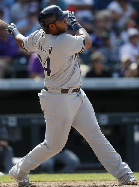 Milwaukee Brewers' Jesus Aguilar follows the flight of his two-run home run off Colorado Rockies relief pitcher Tyler Chatwood in the seventh inning of a baseball game, Sunday, Aug. 20, 2017, in Denver. The Brewers won 8-4. (AP Photo/David Zalubowski)