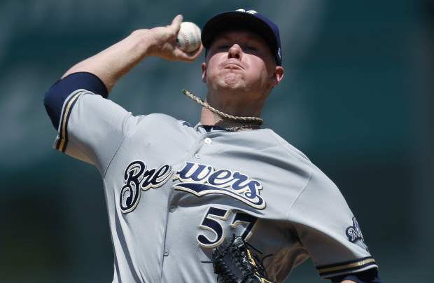 Milwaukee Brewers starting pitcher Chase Anderson delivers a pitch to Colorado Rockies' Charlie Blackmon in the first inning of a baseball game, Sunday, Aug. 20, 2017, in Denver. (AP Photo/David Zalubowski)