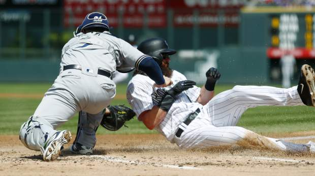 Milwaukee Brewers catcher Manny Pina, left, applies the tag as Colorado Rockies' Charlie Blackmon slides safely across home plate to score from third base on a sacrifice fly hit by Mark Reynolds in the first inning of a baseball game, Sunday, Aug. 20, 2017, in Denver. (AP Photo/David Zalubowski)