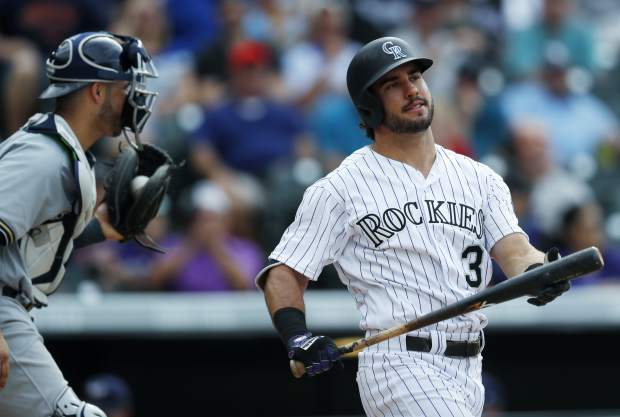 Colorado Rockies pinch-hitter Mike Tauchman, right, reacts after striking out as Milwaukee Brewers catcher Manny Pina heads to the mound to congratulate relief pitcher Corey Knebel to end the bottom of the ninth inning of a baseball game, Sunday, Aug. 20, 2017, in Denver. The Brewers won 8-4. (AP Photo/David Zalubowski)