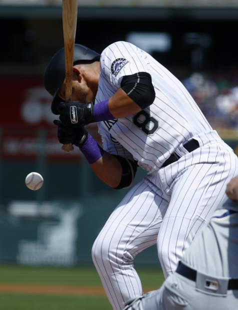 Colorado Rockies' Gerardo Parra reacts after getting hit in the elbow by a pitch thrown by Milwaukee Brewers starting pitcher Chase Anderson in the first inning of a baseball game, Sunday, Aug. 20, 2017, in Denver. (AP Photo/David Zalubowski)