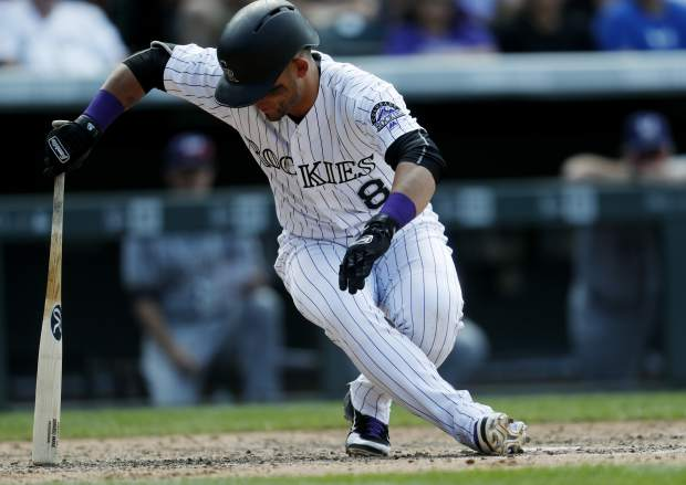 Colorado Rockies' Gerardo Parra uses his bat to avoid falling after swinging at a pitch from Milwaukee Brewers relief pitcher Jared Hughes in the seventh inning of a baseball game Sunday, Aug. 20, 2017, in Denver. Parra ended up striking out to end the inning for the Rockies. The Brewers won 8-4. (AP Photo/David Zalubowski)