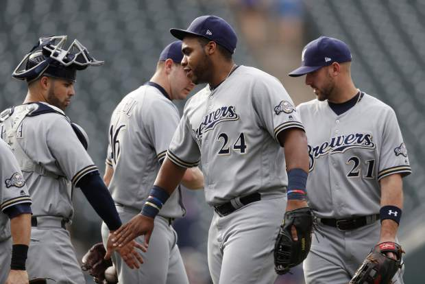 Milwaukee Brewers first baseman Jesus Aguilar, front center, is congratulated by catcher Manny Pina, front left, as relief pitcher Corey Knebel, back left, is congratulated by third baseman Travis Shaw (21) after the Brewers retired the Colorado Rockies in the ninth inning of a baseball game Sunday, Aug. 20, 2017, in Denver. The Brewers won 8-4. (AP Photo/David Zalubowski)