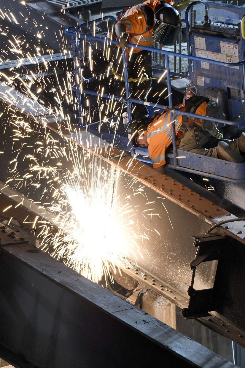 Sparks fly as a pair of construction workers cut through a large I-beam Tuesday evening in Glenwood Springs after girders from the old Grand Avenue bridge fell accidentally.