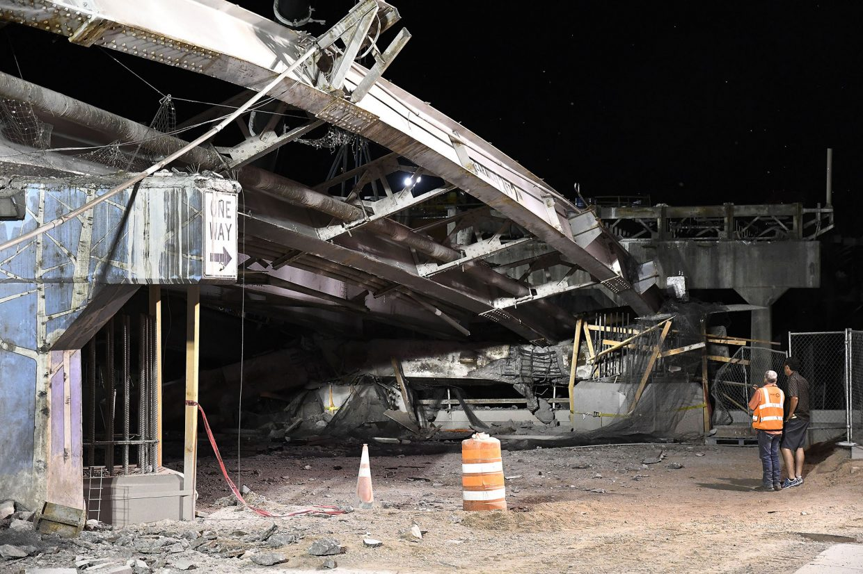 The twisted steel of the under decking of the old Grand Avenue bridge rest on the remains of the concrete pillars after Tuesday's collapse.