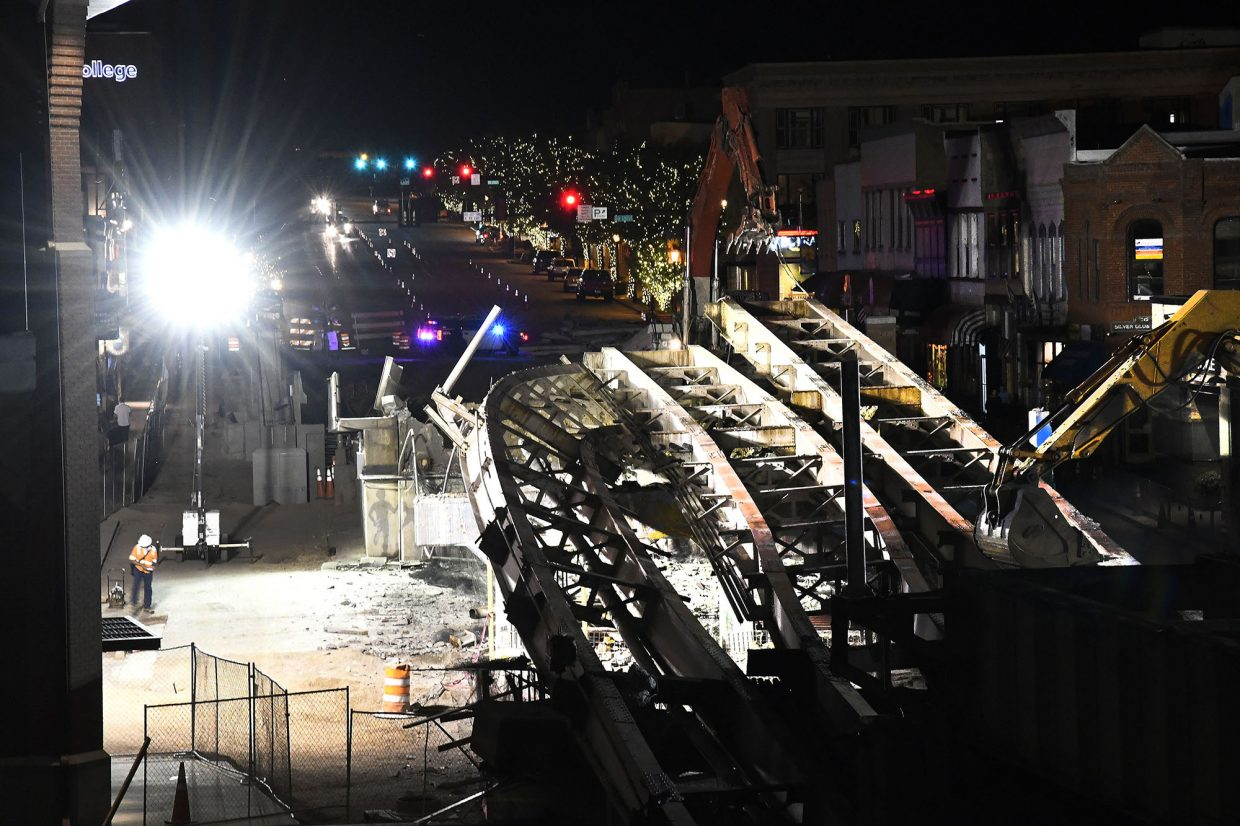 The twisted steel of the old Grand Avenue bridge balances on the remains of the concrete supports after one collapsed during demolition Tuesday.