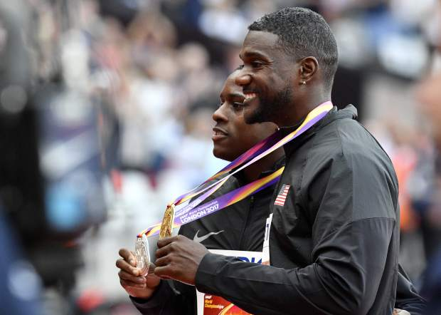 Gold medalist United States' Justin Gatlin, right, stands with compatriot and silver medalist Christian Coleman following the medal ceremony for the Men's 100 meters at the World Athletics Championships in London Sunday, Aug. 6, 2017. (AP Photo/Martin Meissner)