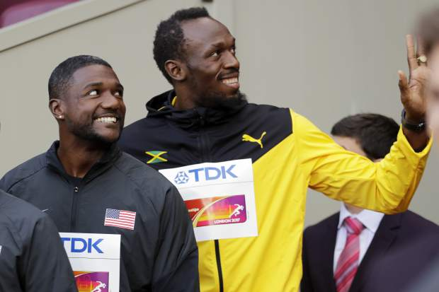 Justin Gatlin of the United States, gold, and Jamaica's Usain Bolt, bronze, from left, smile before the medal ceremony for the Men's 100m during the World Athletics Championships in London Sunday, Aug. 6, 2017. (AP Photo/David J. Phillip)