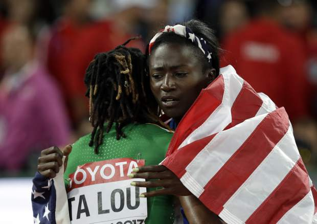Ivory Coast's silver medal winner Marie-Josee Ta Lou, left, and United States' gold medal winner Tori Bowie celebrate after the women's 100m final during the World Athletics Championships in London Sunday, Aug. 6, 2017. (AP Photo/Matthias Schrader)