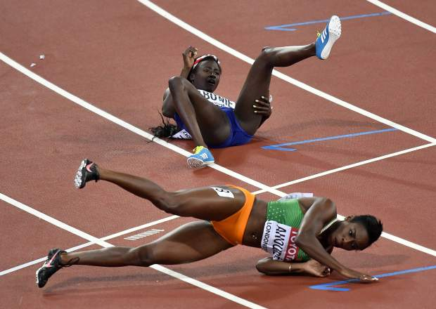United States' Tori Bowie, top, lies on the track after colliding with Ivory Coast's Murielle Ahoure after winning the gold medal in the Women's 100 meters final during the World Athletics Championships in London Sunday, Aug. 6, 2017. (AP Photo/Martin Meissner)
