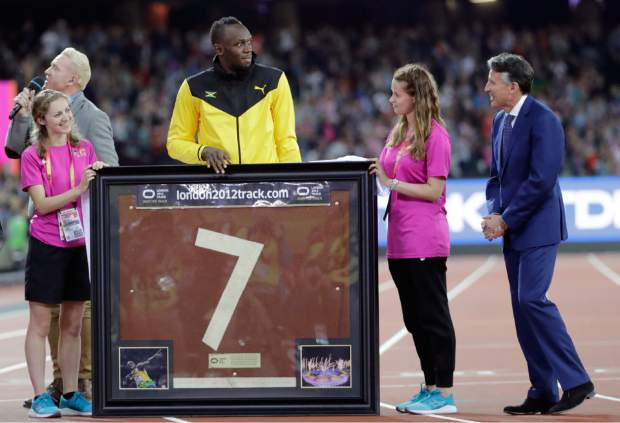 Jamaica's Usain Bolt looks across at IAAF President Sebastian Coe after he was presented with a piece of the track to mark his athletics career during the World Athletics Championships in London Sunday, Aug. 13, 2017. (AP Photo/David J. Phillip)