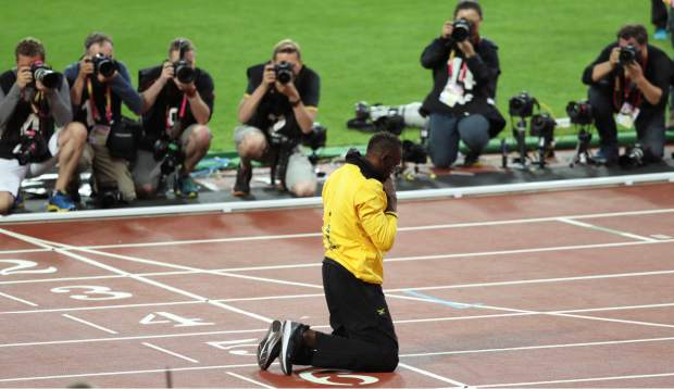 Jamaica's Usain Bolt kneels on the track during his lap of honor at the end of the World Athletics Championships in London Sunday, Aug. 13, 2017. (AP Photo/Leonore Schick)